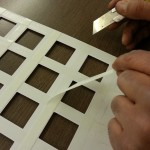 Removing the double-sided tape backing.