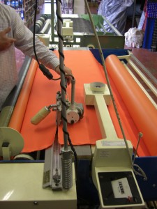 Cutting fabric with fabric rolling machine